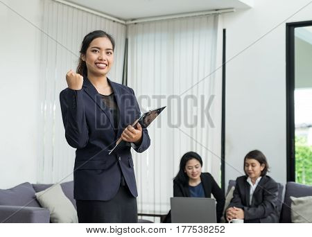 Businesswoman leader arm up for celebrating success with coworkers in officetriumph concept.