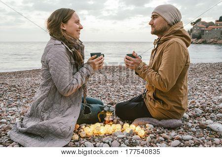 Kinfolk style portrait of Man and woman drinking tea at sunset on the coast of Montenegro