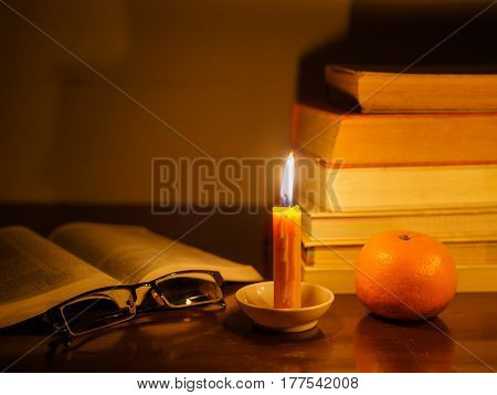 opened book with stack of old tattered book on a wooden table lighted candle and glasses