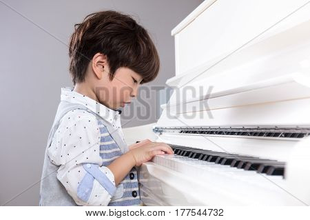 Asian Chinese Little Boy Playing Piano At Home