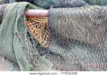 A bunch of old broken fishing nets are lying on the docks