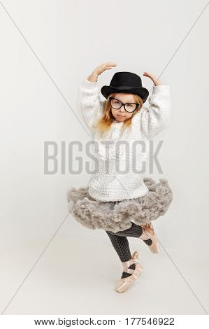 Cute little girl hipster ballerina in a ballet tutu pointes glasses and a hat. The younger generation of dancers.