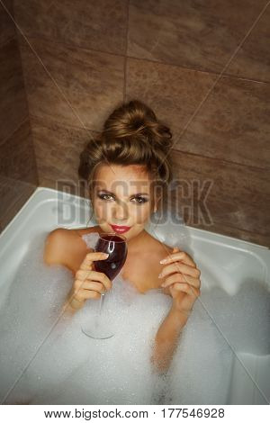 Young cute girl drinking red wine in bath with foam. She relaxes after a hard day. Girl coquettishly looking up
