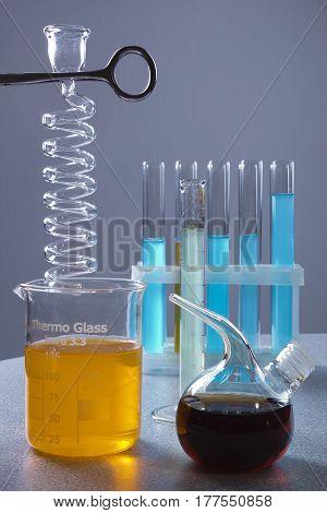 Multicolored liquids in laboratory glassware on a gray background