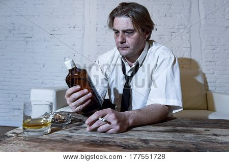 sad depressed alcoholic businessman on his 40s with loose necktie looking wasted and drunk drinking whiskey and smoking at home living room couch in alcoholism problem and alcohol addiction poster