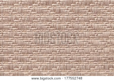 Light brown knitted woolen background with a pattern of soft fleecy cloth. Texture of textile closeup.