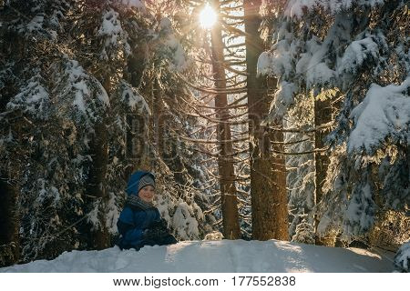 Cute 6 years old boy in Winter fir forest with magical sunlight