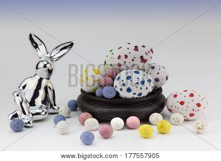 Easter egg background with silver rabbits and speckled easter eggs on white