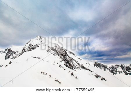 Winter landscape. Snow covered high mountain peaks under cloudy panoramic skies in Europe.