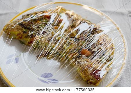 frittata with assorted vegetables wrapped from a plastic film