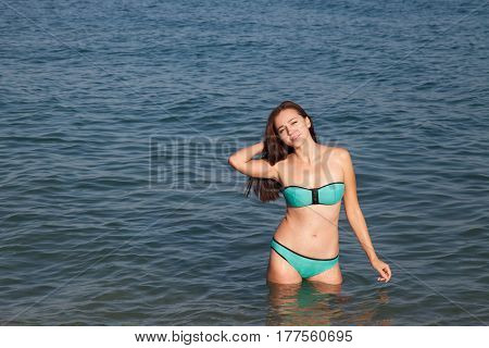 girl in bathing suit stands in the sea and tans