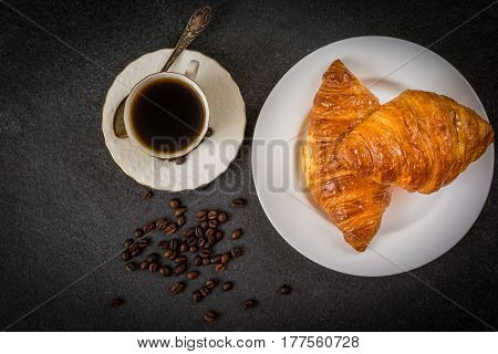 Traditional french breakfast croissant and coffee on black stone table top view
