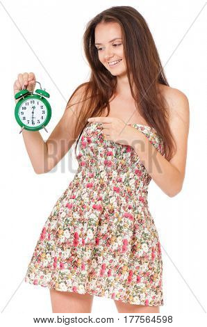 Portrait of a smiling cute teen girl holding alarm clock, isolated on white background