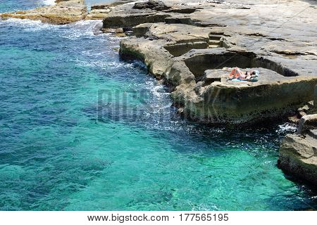 MALTA - APRIL 21: The two women are on beach on April 21 2015 in Malta. More then 16 mln tourists is expected to visit Malta in year 2015.