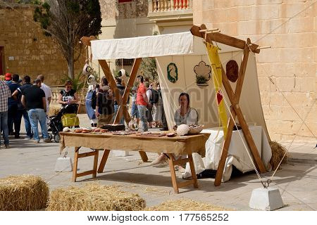 MDINA MALTA - APRIL 19: The women sells souvenirs at Mdina medieval festival and tourists on April 19 2015 in Mdina Malta. More then 16 mln tourists is expected to visit Malta in year 2015.