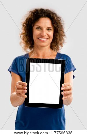 Beautiful middle aged woman holding and showing something on a tablet