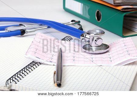 Folder file, stethoscope and RX prescription on the desk. blurred background