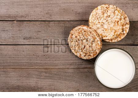 glass of milk with grain crispbreads on old wooden background with copy space for your text. Top view.