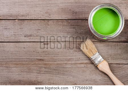 green paint in the bank to repair and paint brush on the old wooden background with copy space for your text. Top view.