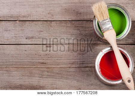 green and red paint in the bank to repair with paint brush on the old wooden background with copy space for your text. Top view.