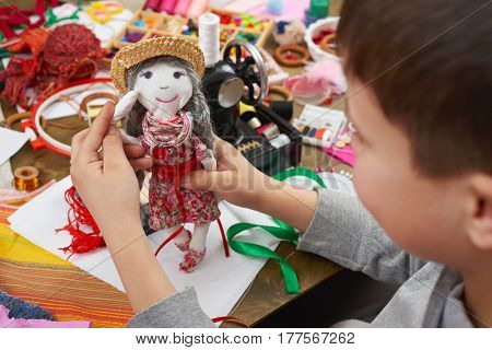 boy tailor learns to sew, dress for doll, handmade and handicraft concept
