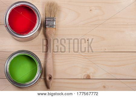 green and red paint in the bank to repair with paint brush on the light wooden background with copy space for your text. Top view.