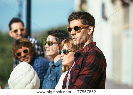 Group of trendy young people wearing casual clothing and sunglasses standing and looking away.