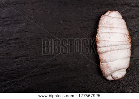one croissant sprinkled with powdered sugar on black stone background with copy space for your text. Top view.
