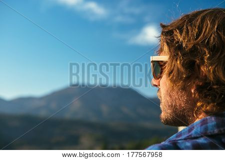 Side view of young handsome male wearing sunglasses and looking away on background of landscape.