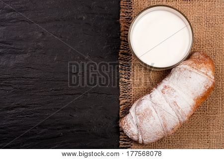 glass of milk with croissants on black stone background. with copy space for your text. Top view.