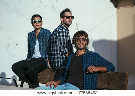 Group of three young stylish men in shirts and sunglasses sitting on bench and looking away.