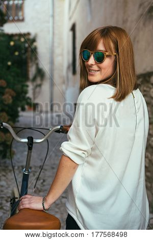 Young girl wearing sunglasses standing near retro bicycle and smiling over shoulder at camera.