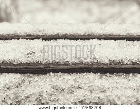 Late snow with hailstones on the old bench, black and white spring