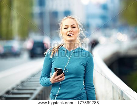 Young blonde woman is relaxing after jogging and listening music.