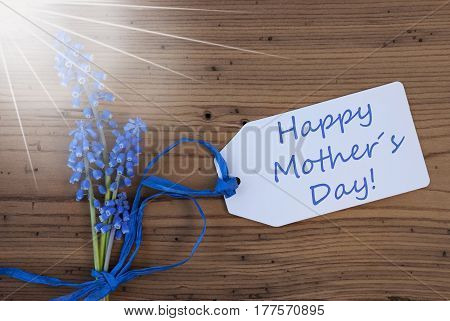 Label With English Text Happy Mothers Day. Sunny Blue Spring Grape Hyacinth With Ribbon. Aged, Rustic Wodden Background. Greeting Card For Spring Season
