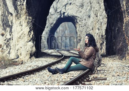 Teenage girl sits on railroad and throwing a rock. Bored girl on a railway track