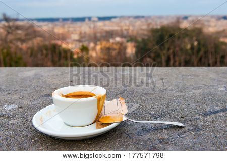 A traditional Italian espresso on a concrete ledge. The city of Rome is blurred in the background.
