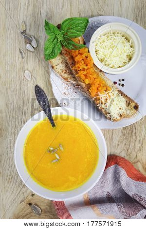 Carrot soup with bread topped and grated cheese. Top view