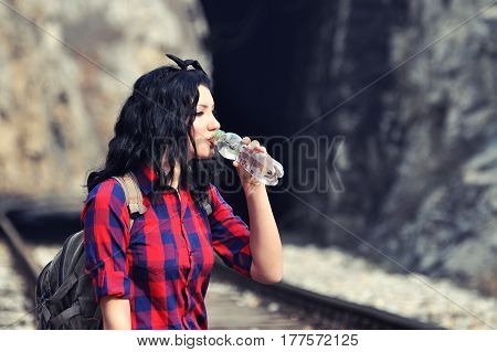 Girl drinking water on railway line. Teenage girl drink water from plastic bottle
