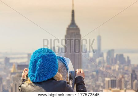 Woman enjoying in New York City panoramic view. Manhattan downtown skyline with illuminated Empire State Building and skyscrapers seen from observation deck terrace.
