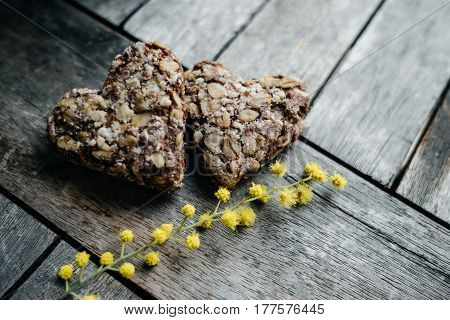 Couple Cookies In The Shape Of Hearts With Sprigs Of Mimosa. Spring Concept