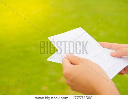 hands holding saving account passbook, book bank on the green grass background