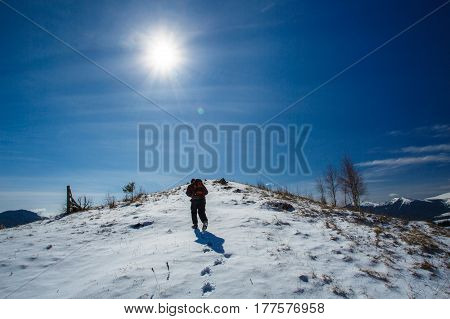 tourist goes on snowy mountain top in winter