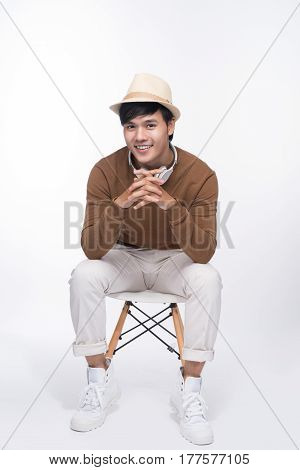 Smart casual asian man seated on chair posing while looking away in studio background
