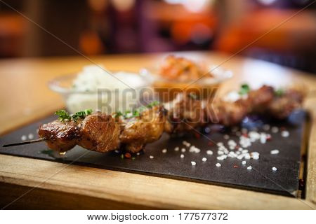 Iberian pork shish kebab with onion salad and sauce seved on a stone board