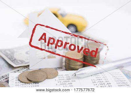 Approved mortgage loan agreement application with car house and gold coin.