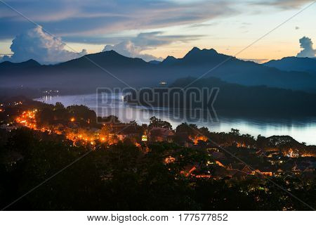 Luang Prabang, Laos. Aerial view of Luang Prabang town in Laos. Night over the small city surrounded by mountains. River and colorful sunset sky