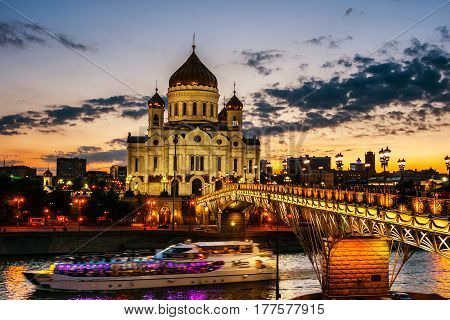 Moscow, Russia. Sun is setting down behind the famous landmark - Cathedral of Christ the Savior, Moscow, Russia. Touristic boats going down the river