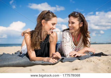 Two Beautiful Female Friends Lying On Beach Laughing