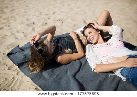 Two Female Friends Lying Together On Beach Laughing